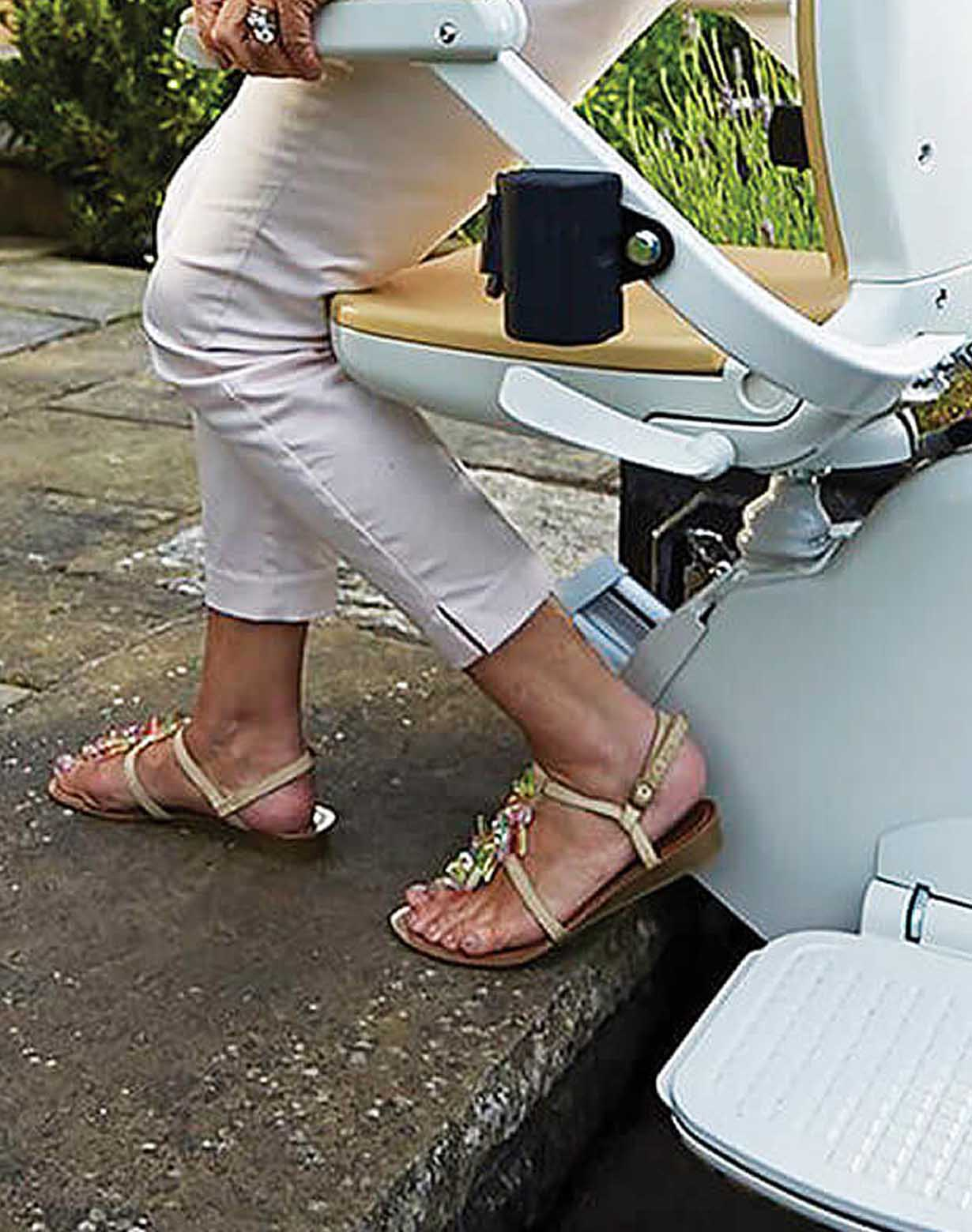 Lady getting off outdoor straight stairlift she has swivelled the seat to safely dismount