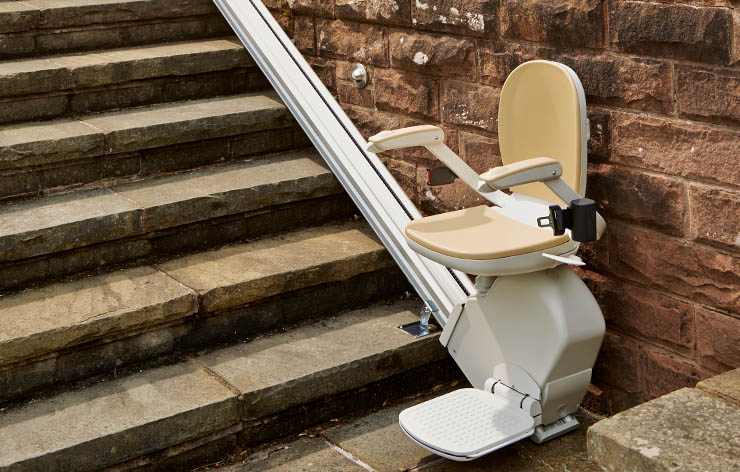 Outdoor stairlift fixed to the concrete steps in the garden