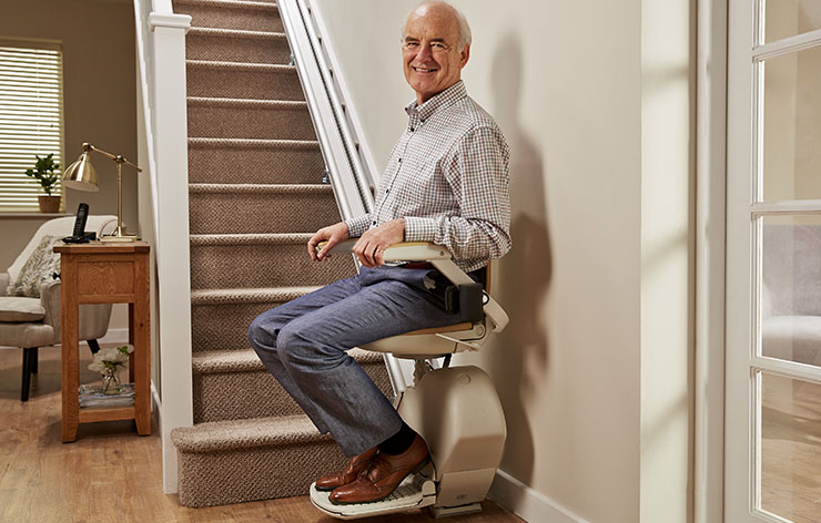 Man sitting on a straight stairlift at the bottom of the stairs
