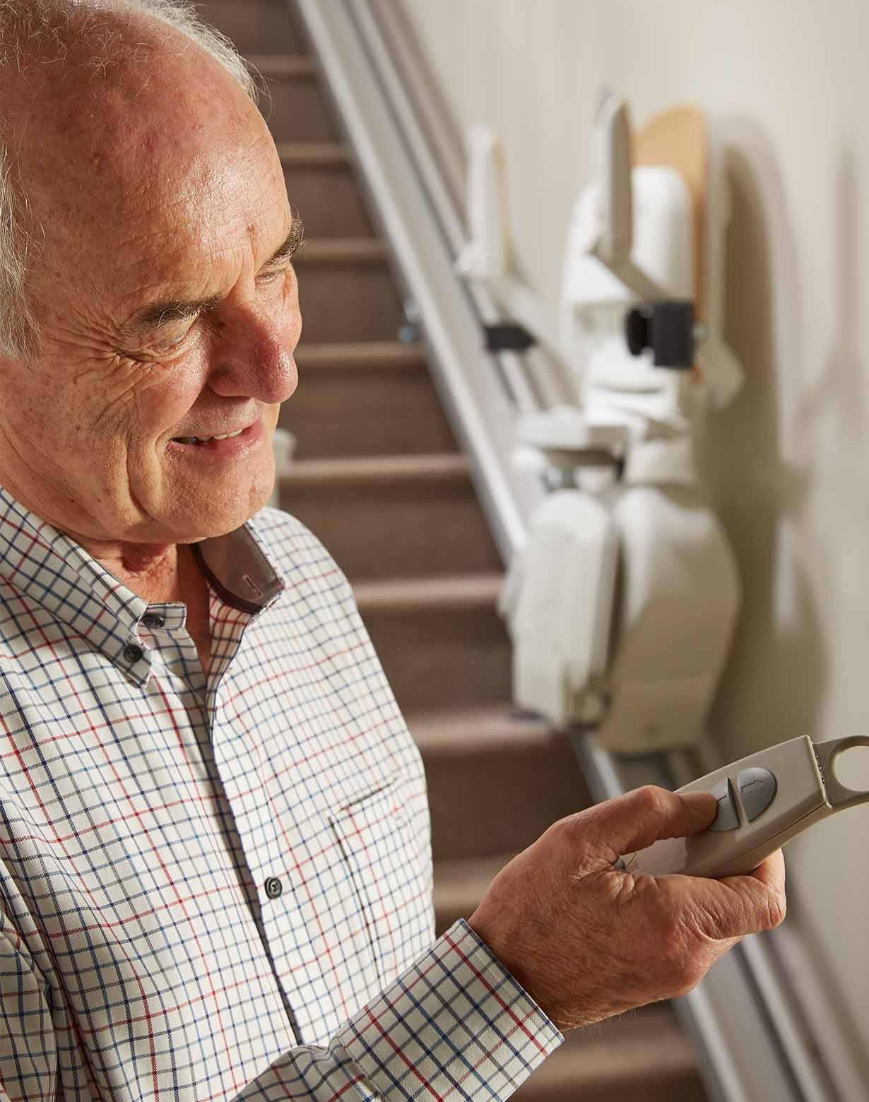 Man calling his straight stairlift down with a remote control